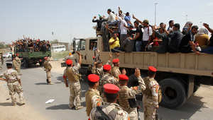 متطوعون في سيارة عسكرية للالتحاق بمراكز التجنيد للانخراط في القتال ضد داعش