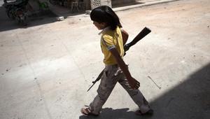 صورة أرشيفية لطفل سوري يحمل بندقية