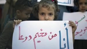 """طفلة سورية تحمل لافتة كتب عليها """"أنا من مخيم درعا"""""""