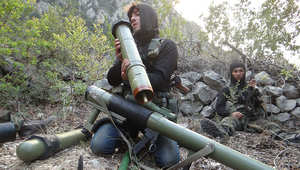 أحد المقاتلين السوريين يتفقد إحدى القذائف في كسب
