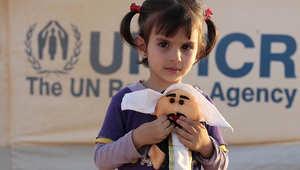 طفلة سورية تحمل دميتها في مخيم الزعتري بالأردن