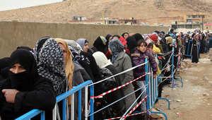 مجموعة من اللاجئين السوريين يقفون في طابور طويل للتسجيل في مخيم للاجئين بتركيا