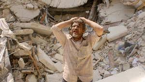 سوري يبدو مذهولا عقب نجاته من قصف دمر ما حوله