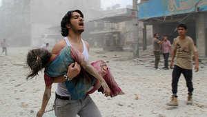 شاب سوري يحمل طفلة أصيبت نتيجة للقصف بالبراميل المتفجرة في حلب