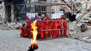 شاهد بالصور: أطفال دوما في قفص وشعلة النيران تنتظر لإحراقهم مثل الكساسبة باحتجاج على قصف الأسد