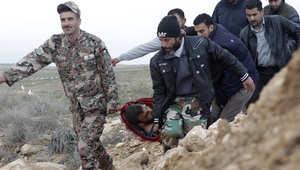 جندي أردني ولاجئون سوريون يحملون جريحا عبر الحدود
