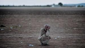 لاجئ كردي في منطقة عين العرب بين الحدود التركية والسورية