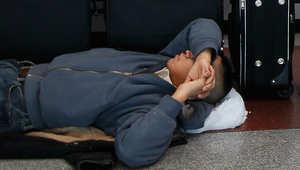 أحد الركاب ينام على أرضية قاعة الانتظار في مطار نيويورك