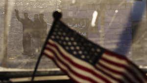 عراقيون يلوحون بدواع قوات أمريكية اثناء انسحابها من العراق في 2011