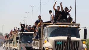 متطوعون عراقيون على متن مركبات عسكرية في بغداد
