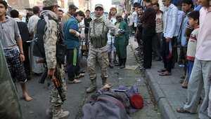 جنود ومواطنون يتجمعون حول جثة قائد عسكري يمني قتل اثناء سيره بالشارع في العاصمة صنعاء الاثنين 5 مايو/ أيار 2014.