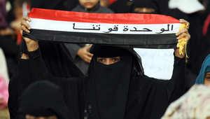 يمنية ترفع شعارا اثناء مسيرة مؤيدة للحكومة