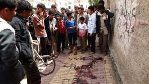 يمنيون يتجمعون حول آثار الدماء التي خلفتها محاولة اغتيال استاذ القانون الإسلامي اسماعيل الوزير في صنعاء 8 أبريل/ نيسان 2014